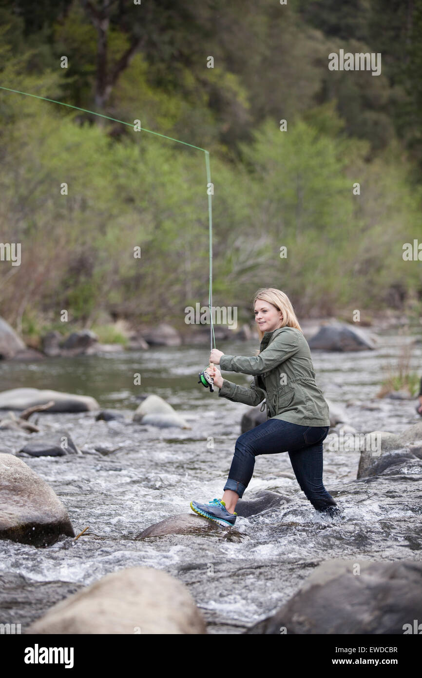 A young, adventurous woman fly fishing in the fast moving current of the Feather River  in the Sierra Nevada Mountains - Stock Image