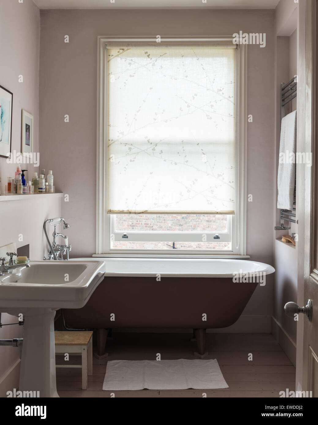 Free standing roll top bath in bathroom with wooden flooring and ...