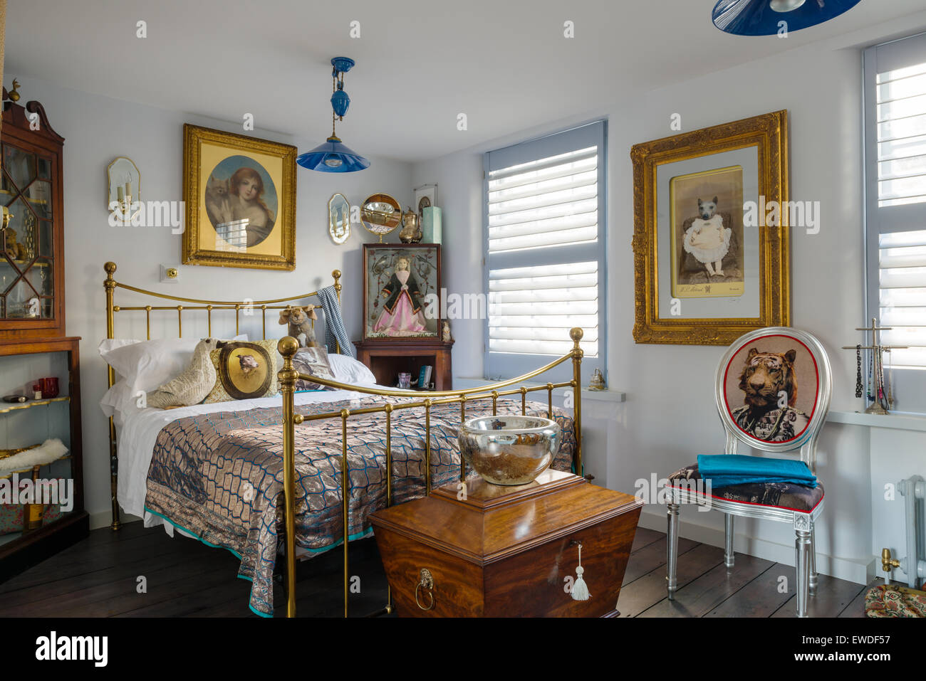 Brass framed bedstead in elegant bedroom with antique wine cooler and Visitorian dining chair - Stock Image