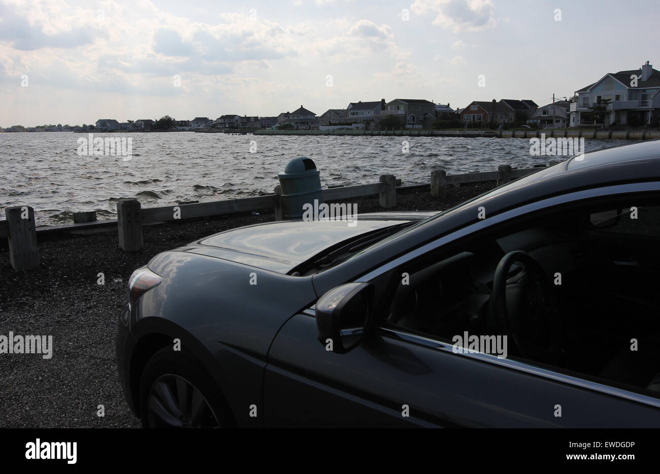 Parked car by the water's edge - Stock Image