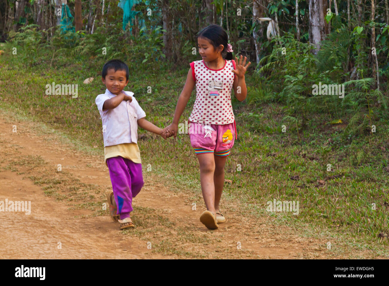 LAOTIAN brother and sister walk on the BOLAVEN PLATEAU near PAKSE - SOUTHERN, LAOS - Stock Image