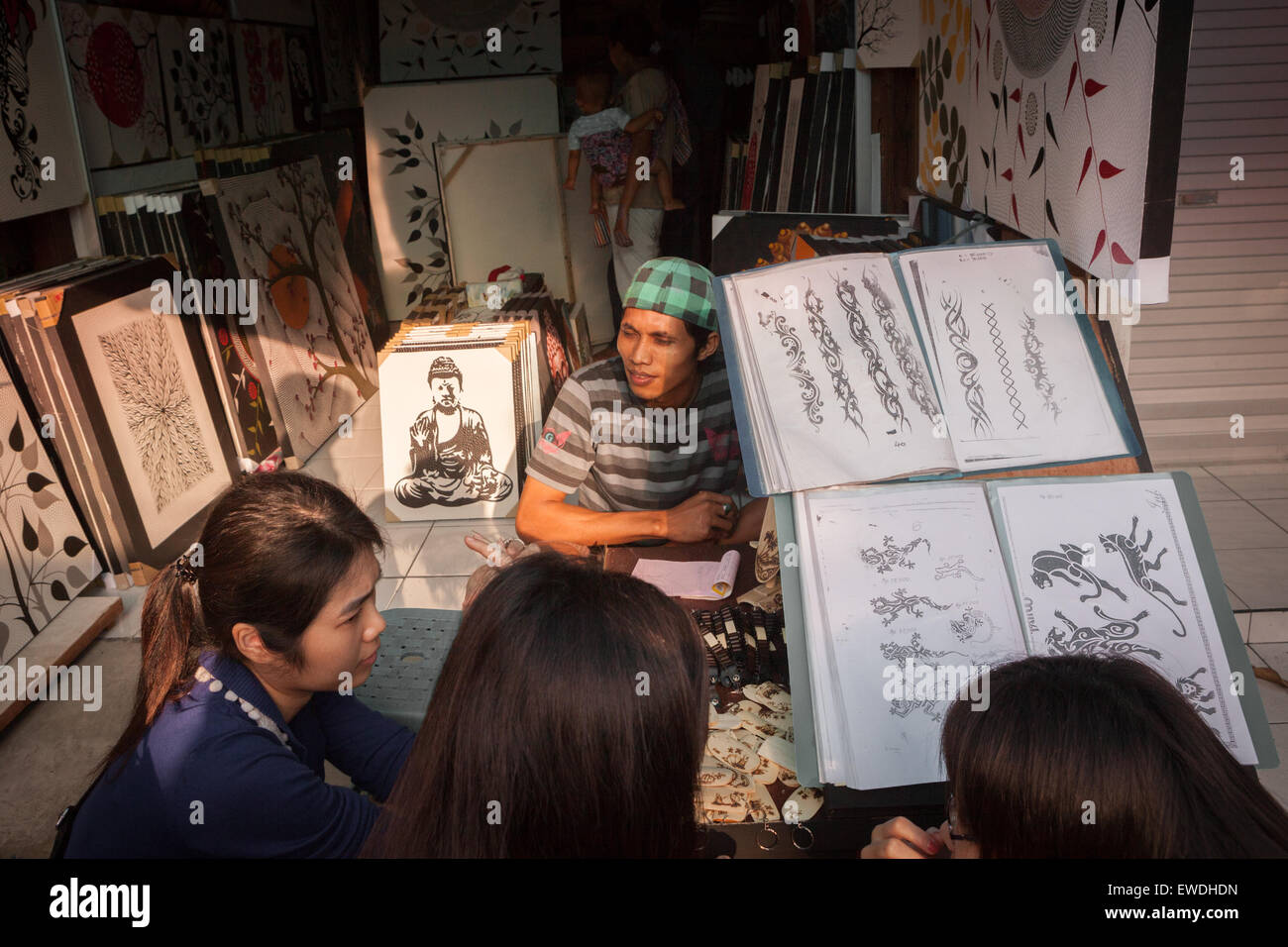 Tourists take a look of tattoo designs at tattoo vendor. - Stock Image