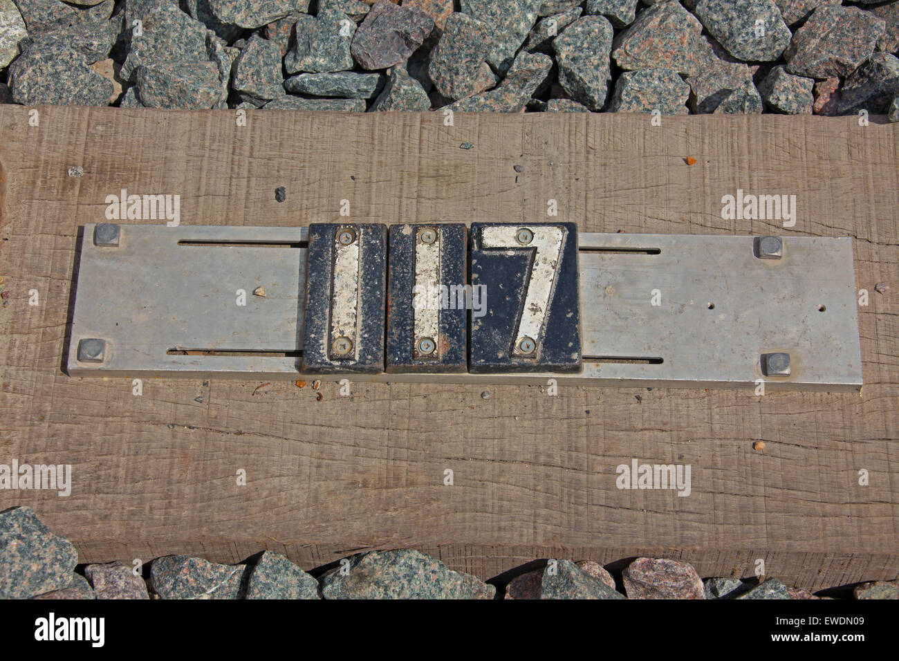 Cast Iron numbers on a steel mount on a wooden sleeper. - Stock Image
