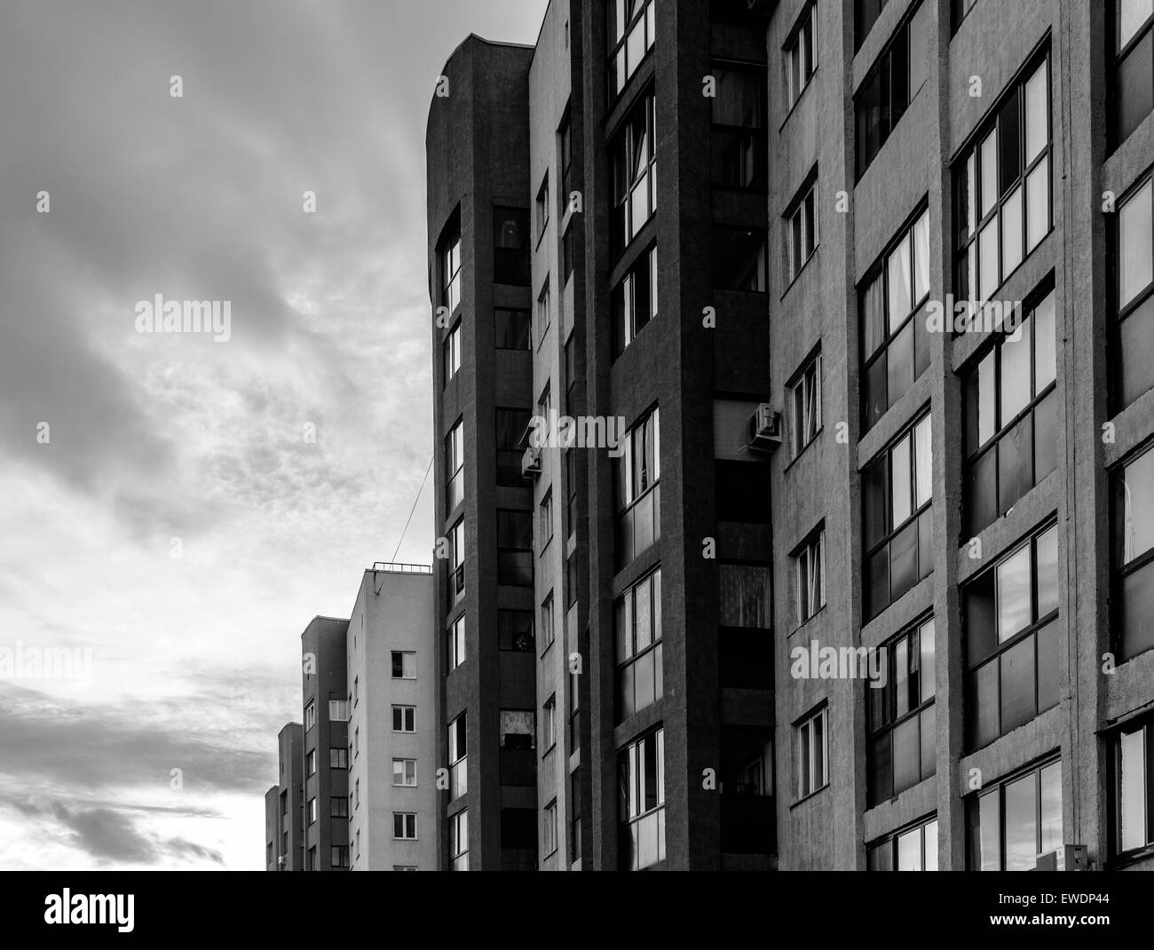 Big housing apartments with a sunset sky in the background - Stock Image
