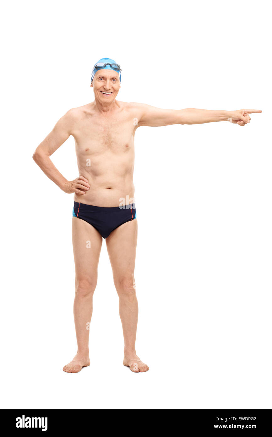 Full length portrait of a senior man in black swim trunks pointing with his hand towards right and looking at the - Stock Image