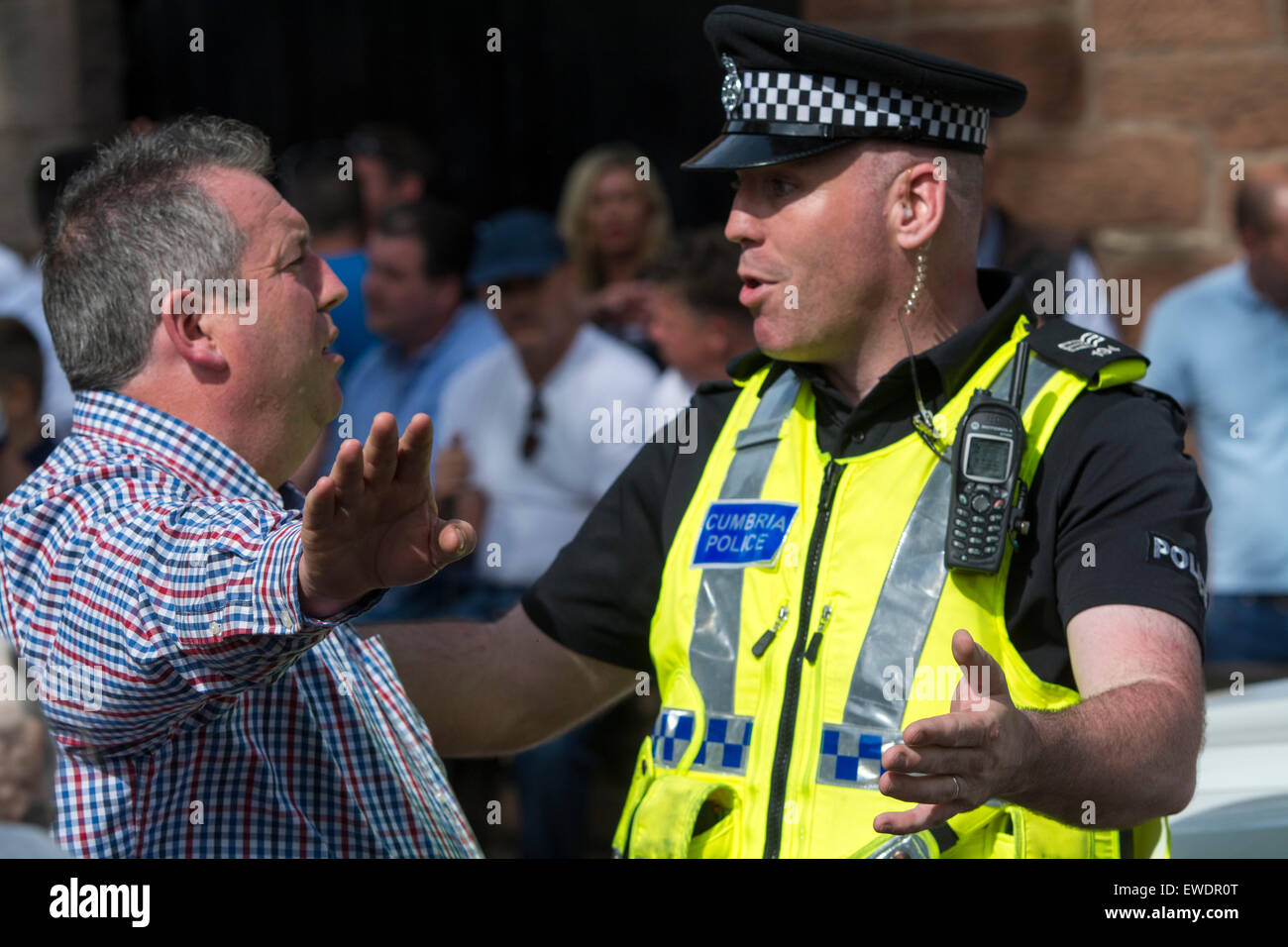 Police man and a horse owner having a discussion about where horses can be left in the town. Appleby Horse Fair - Stock Image