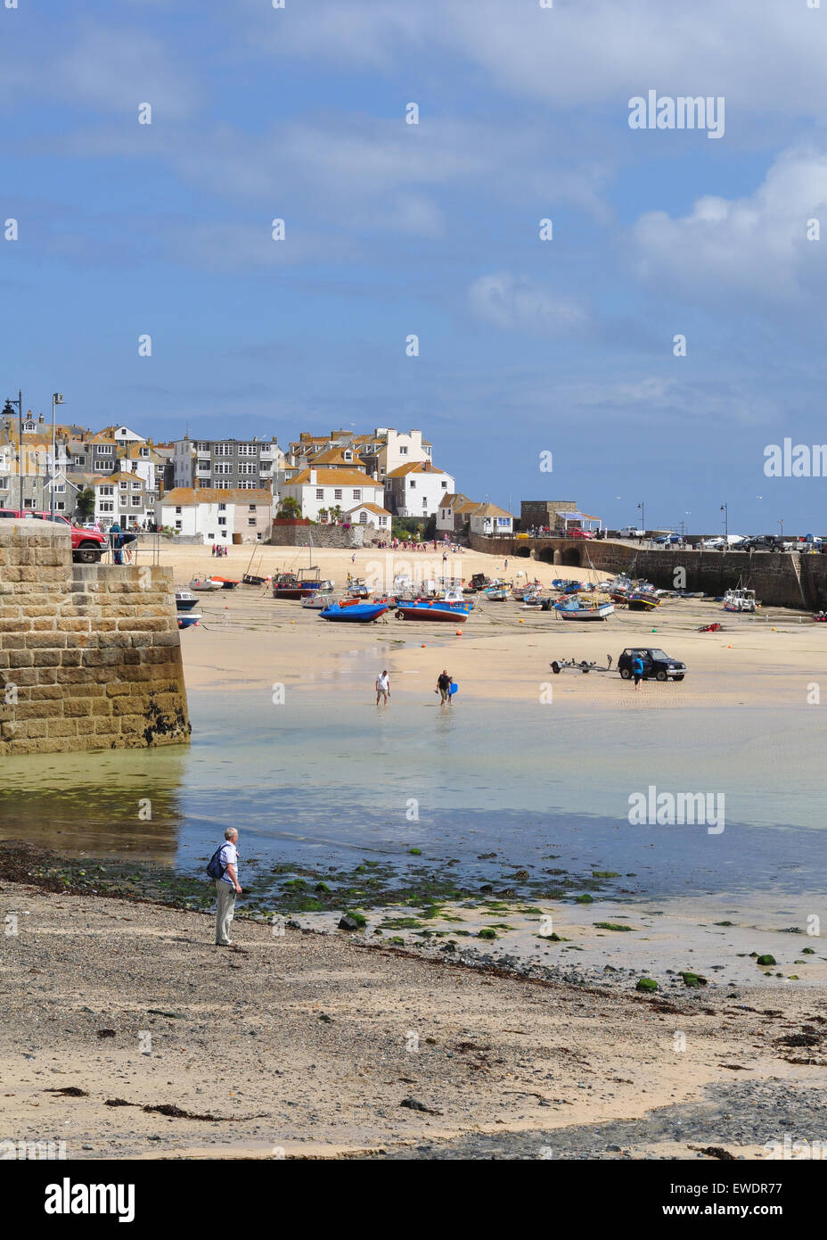 St Ives, Cornwall, England, UK.  Holidaymakers at the harbour waterfront at low tide Stock Photo