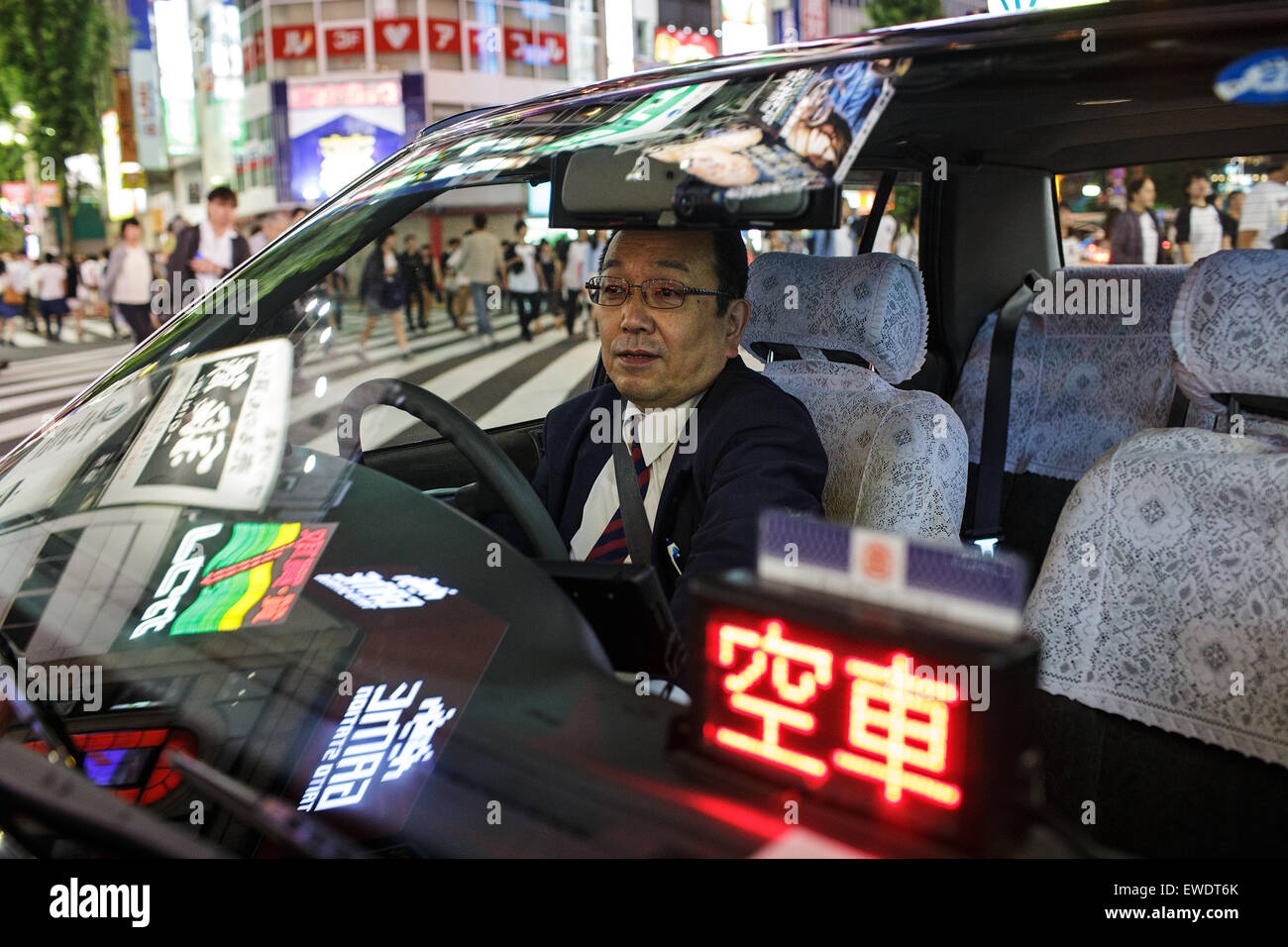 A taxi driver inside his car at night in Shinjuku, Tokyo, Japan Stock Photo