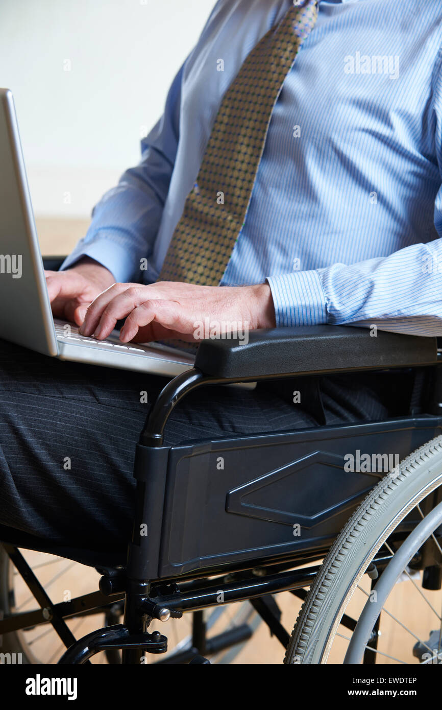 Disabled Businessman In Wheelchair Using Laptop - Stock Image