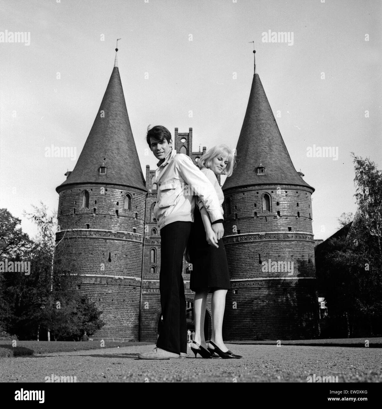 Ein Paar vor dem Holstentor in Lübeck, Deutschland 1960er Jahre. A couple in front of the Holstentor gate at Luebeck, Stock Photo