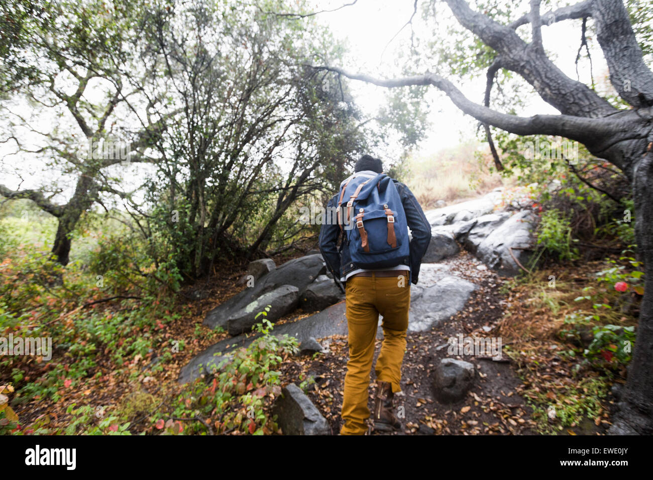 Young man carrying a backpack hiking - Stock Image