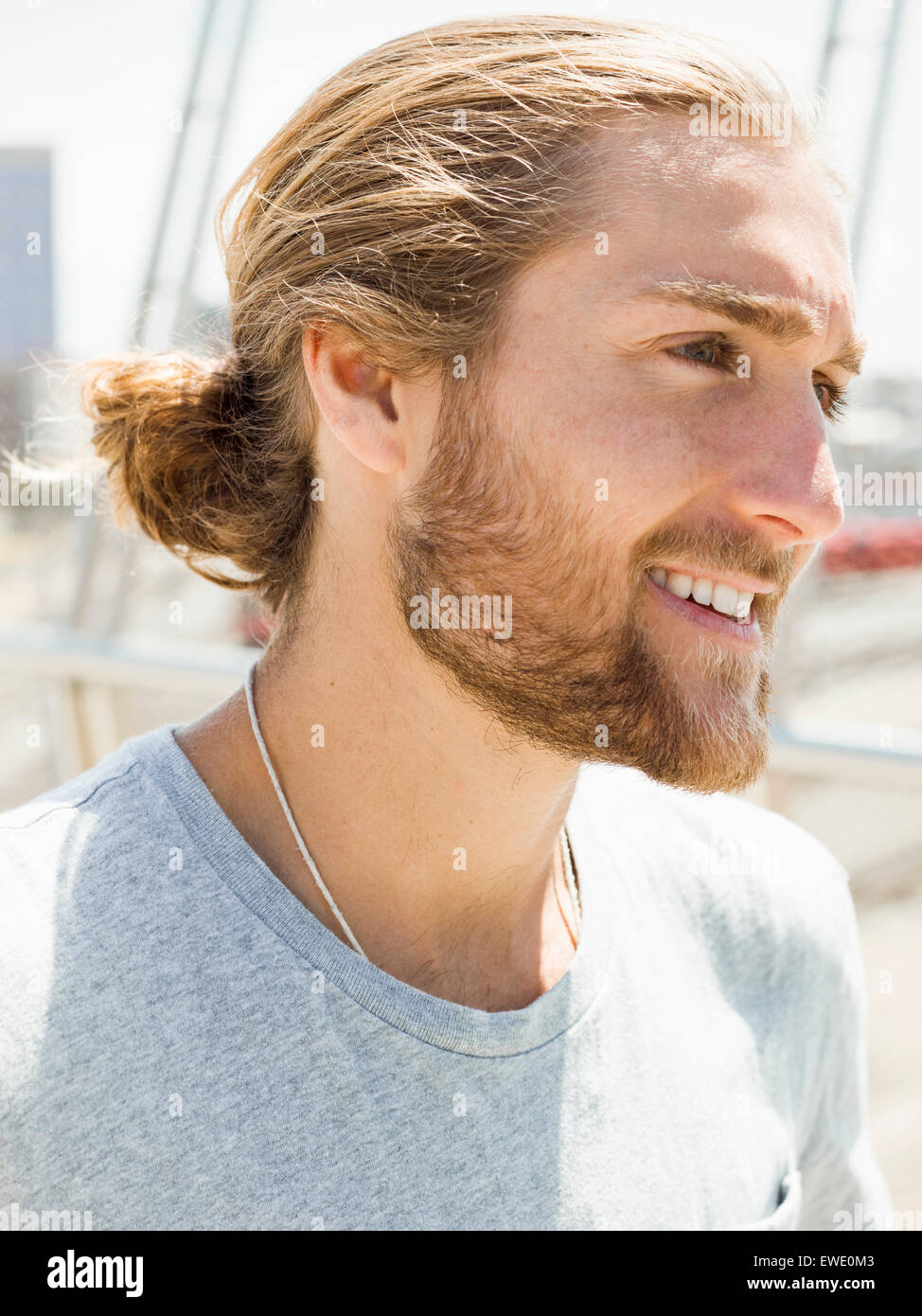 A young man with beard, red hair and ponytail - Stock Image