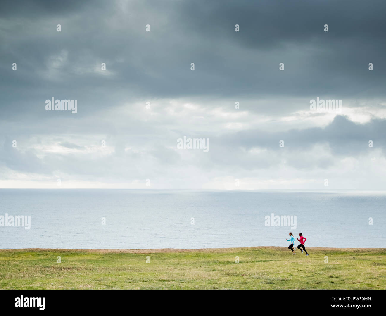 Two women jogging along the coast runners Stock Photo