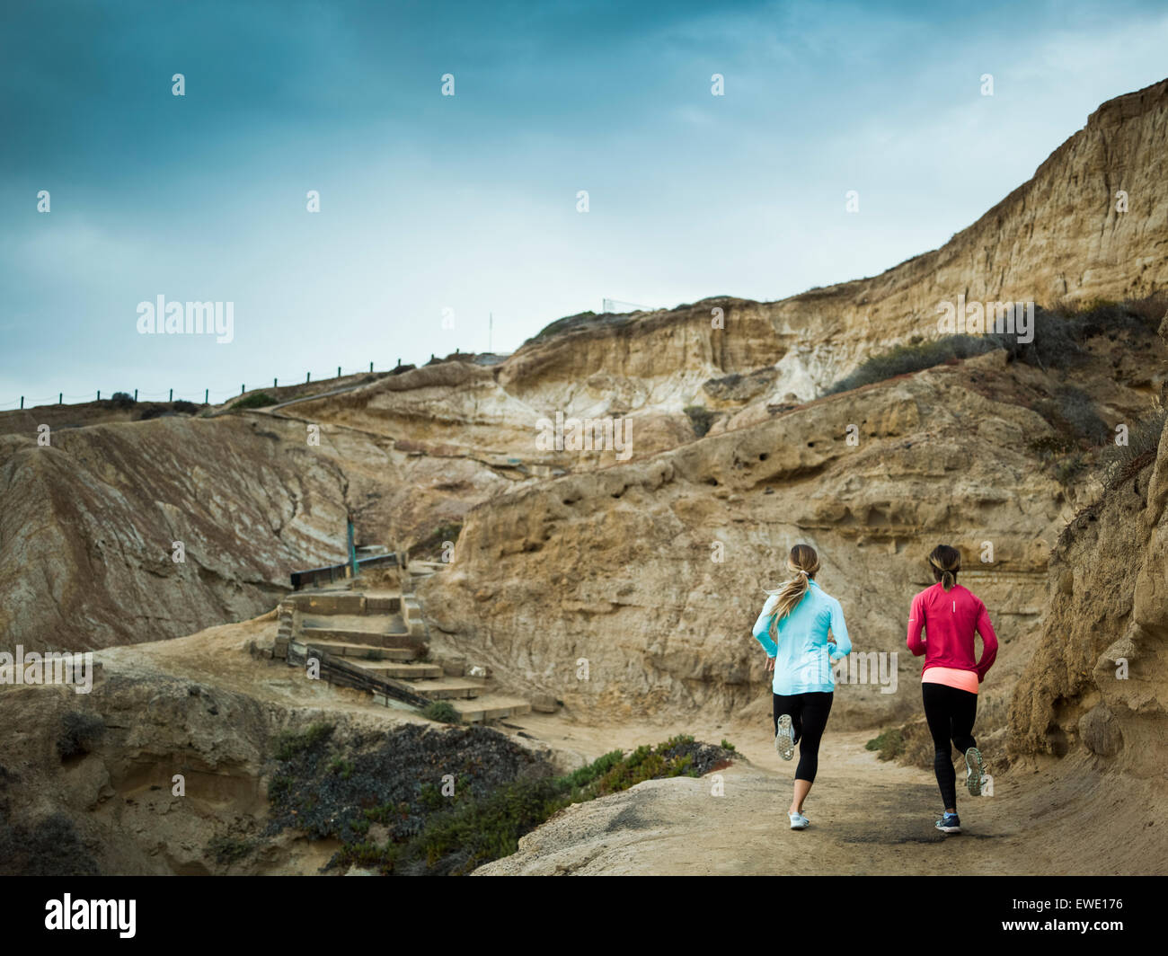 Two women jogging along a quarry trail - Stock Image