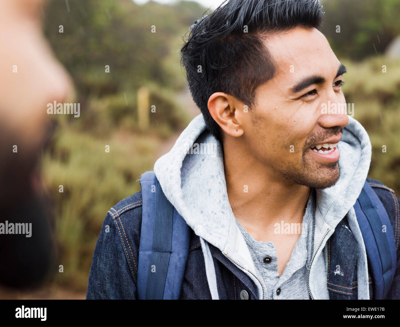 Two men, one smiling wearing a hooded top - Stock Image