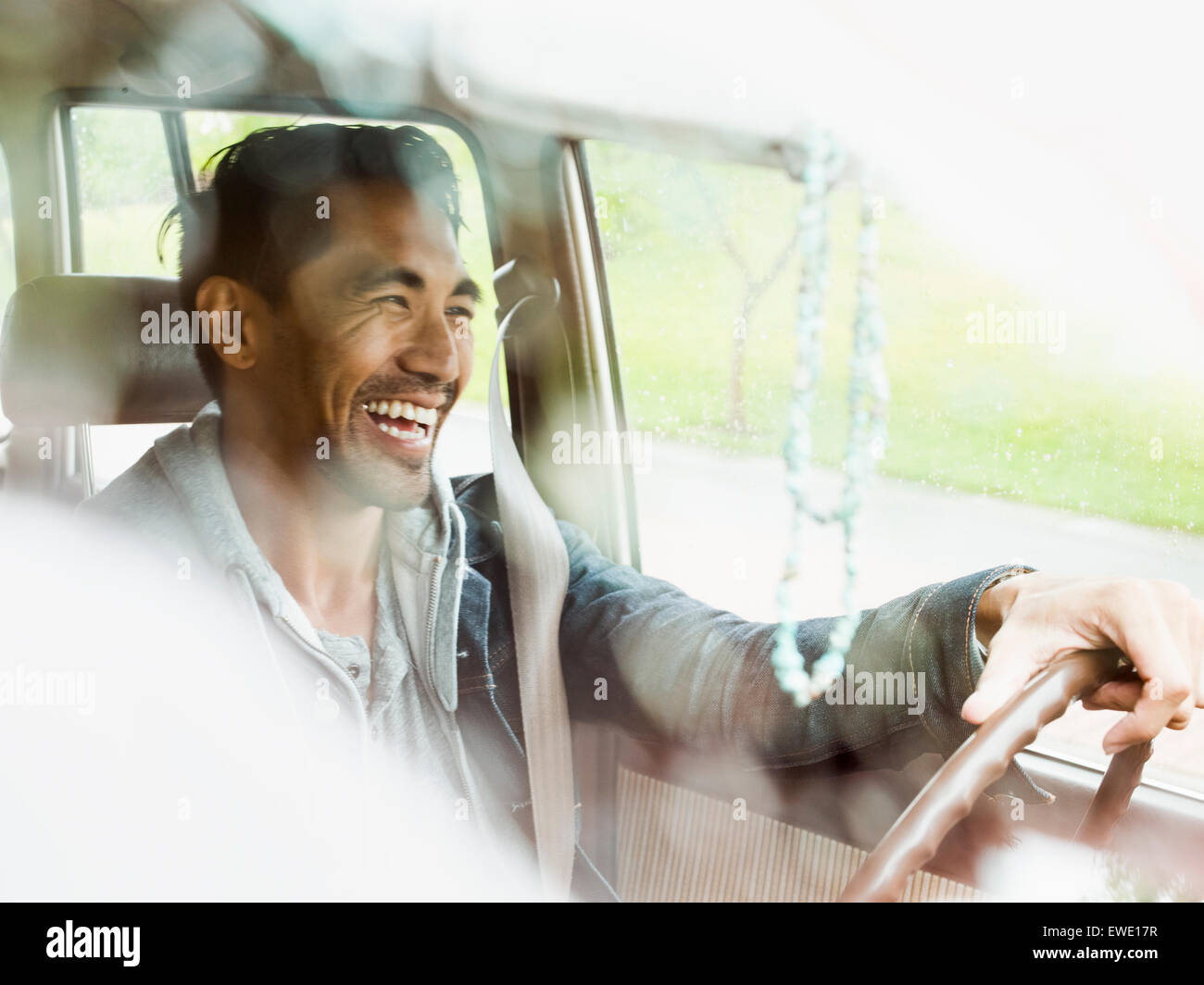 Young man in a car behind the steering wheel, driving - Stock Image
