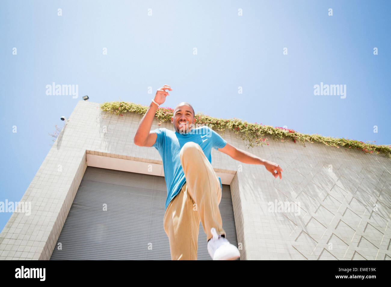 Young man jumping in the air on street parcour parkour - Stock Image