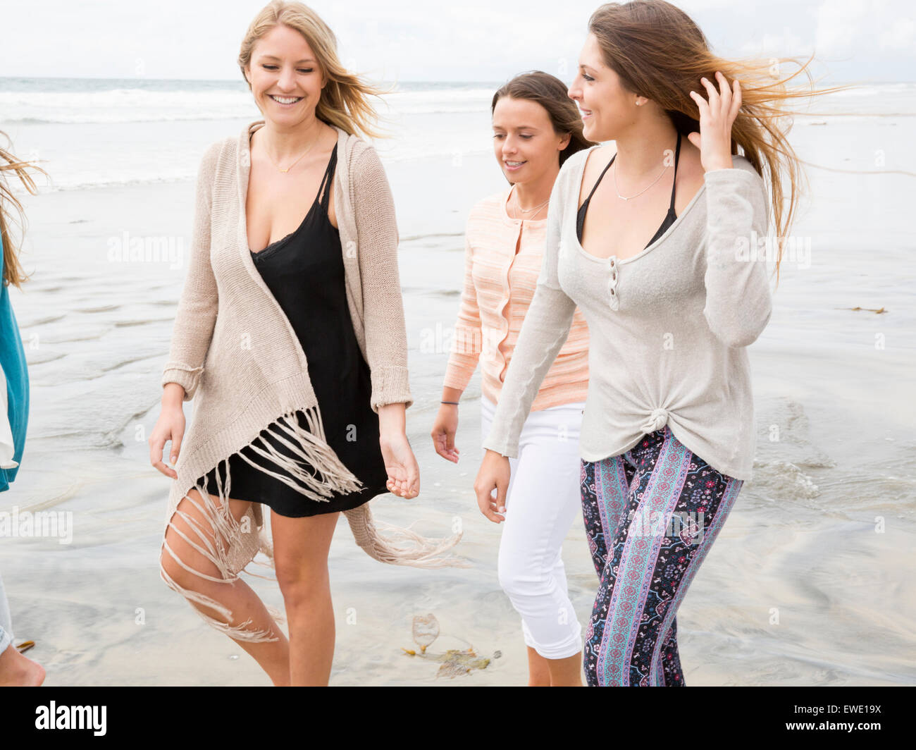 Three smiling young women walking on a beach - Stock Image