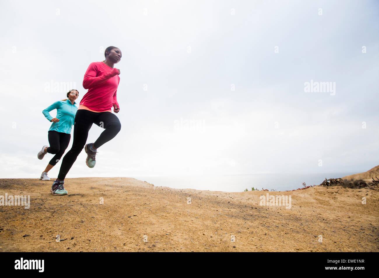 Two women jogging along the coast exercise - Stock Image