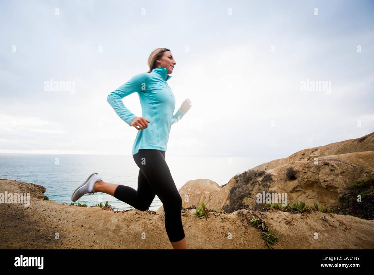 A young woman jogging along the coastal cliffs usa - Stock Image