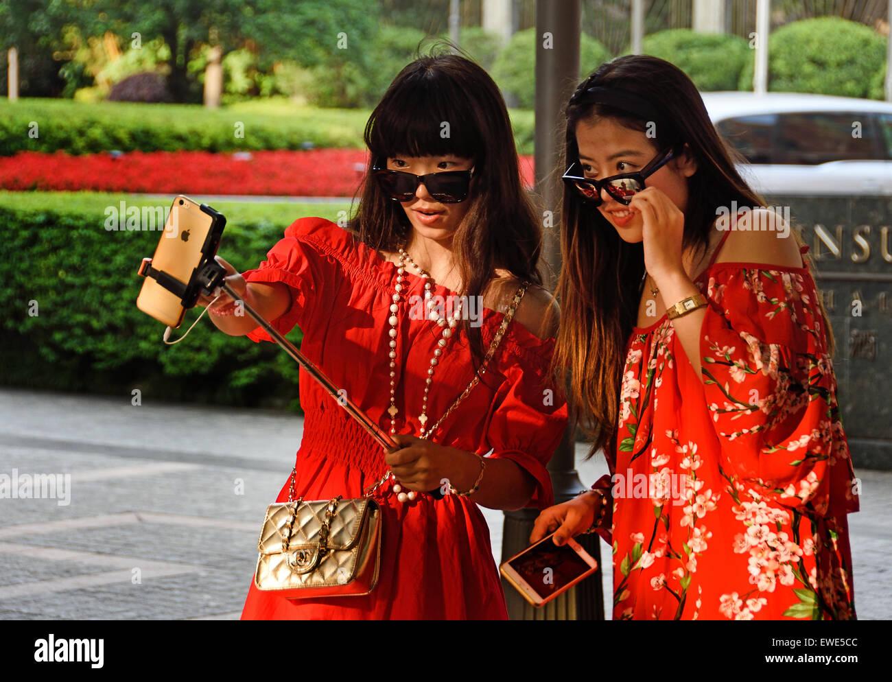 selfie stick photo attractive beautiful young  women Shanghai China Chinese - Stock Image
