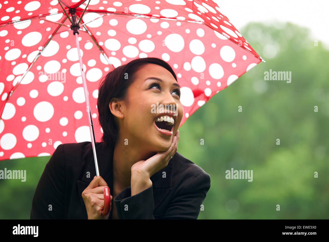 Young Woman Sheltering From Rain Under Umbrella - Stock Image