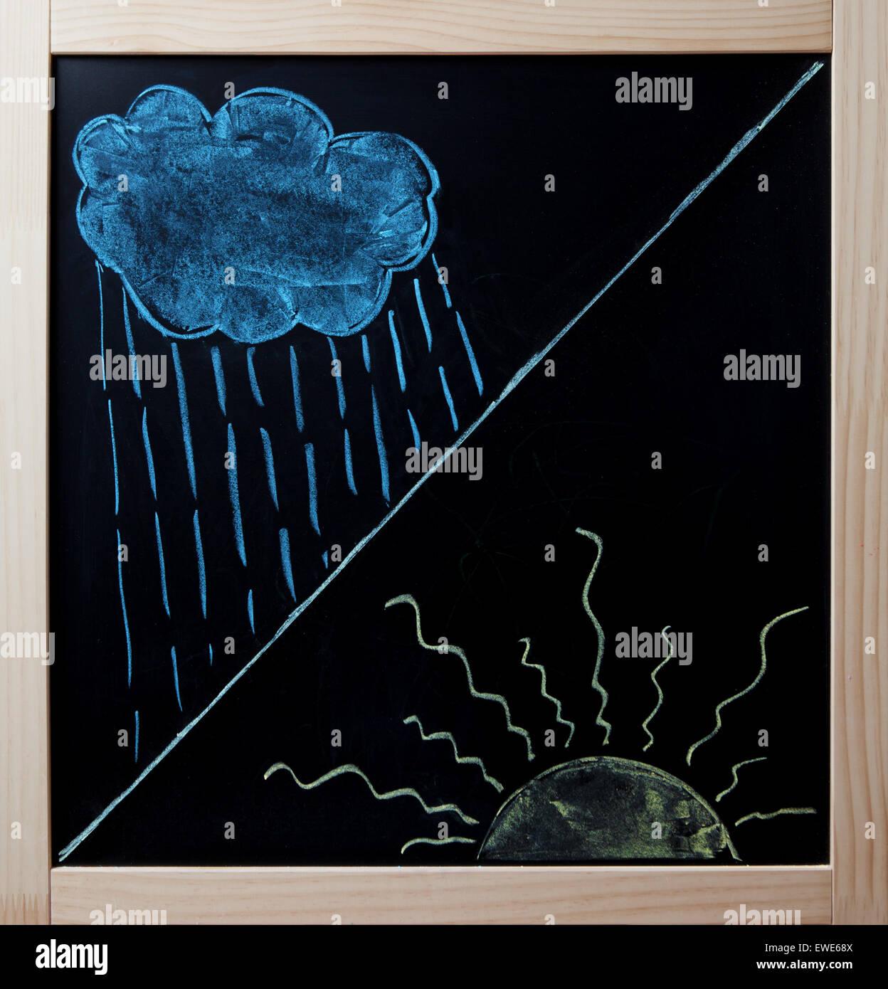 Rain cloud and beaming sun drawn on blackboard. - Stock Image