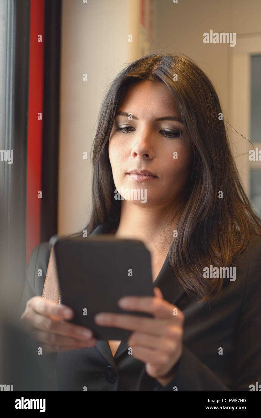 A portrait of attractive brunette woman using tablet in train, while commuting from work - Stock Image