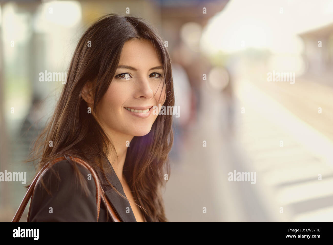 Smiling brunette woman standing in a train station in the morning, commuting to work in an eco-friendly manner - Stock Image