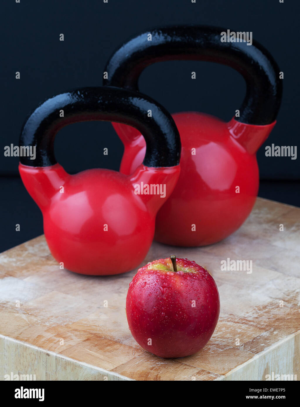 Red apple and kettlebells on chopping board. - Stock Image