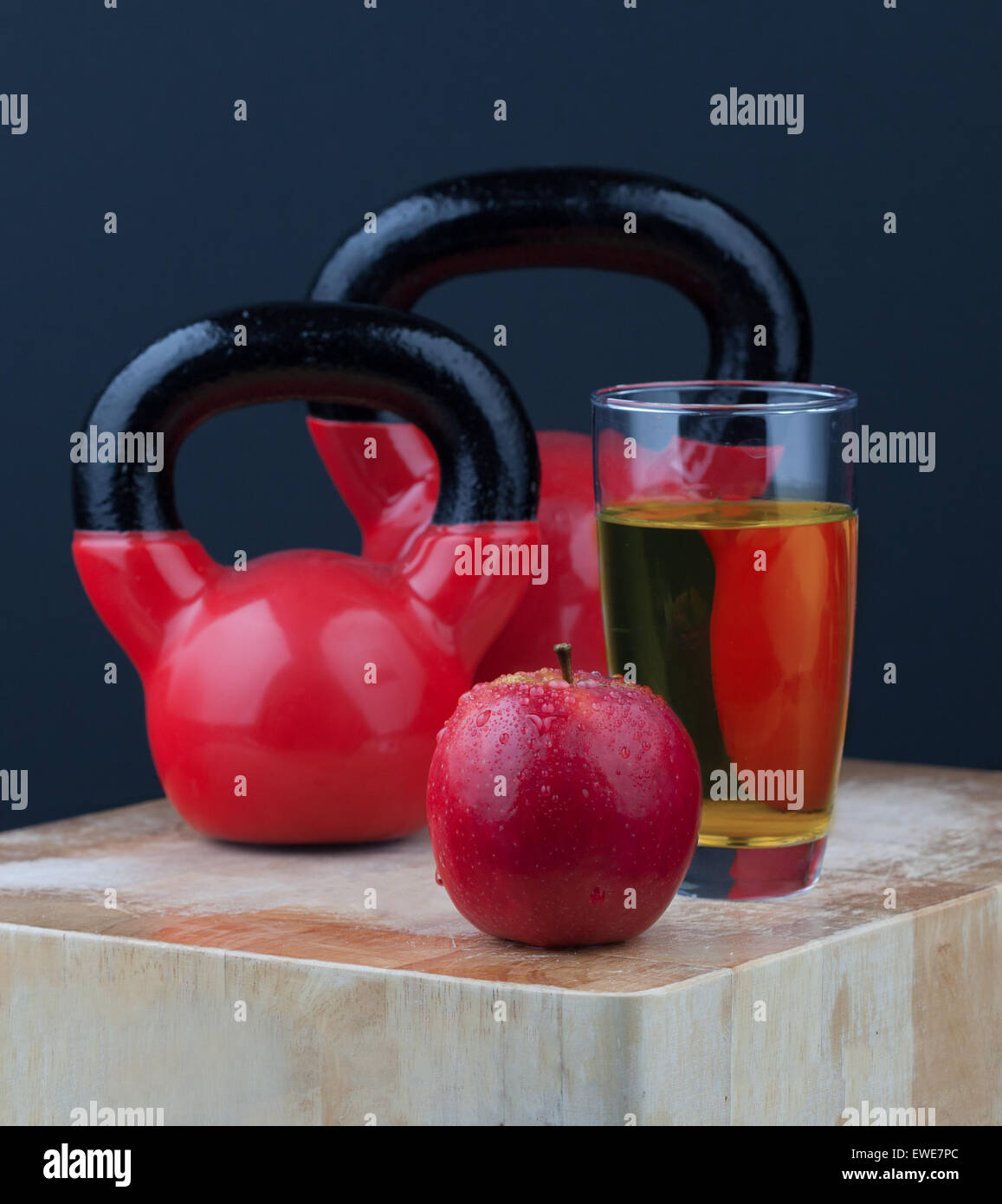 Red apple, juice, and kettlebells on chopping board - Stock Image
