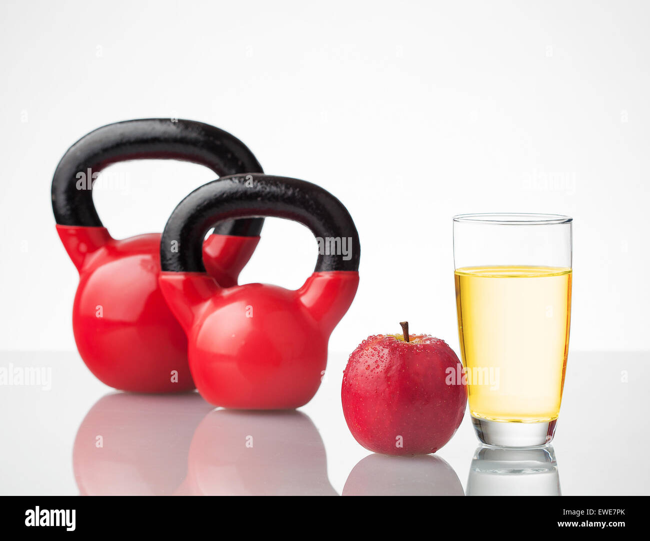 Red apple, juice, and kettlebells on reflective surface. - Stock Image