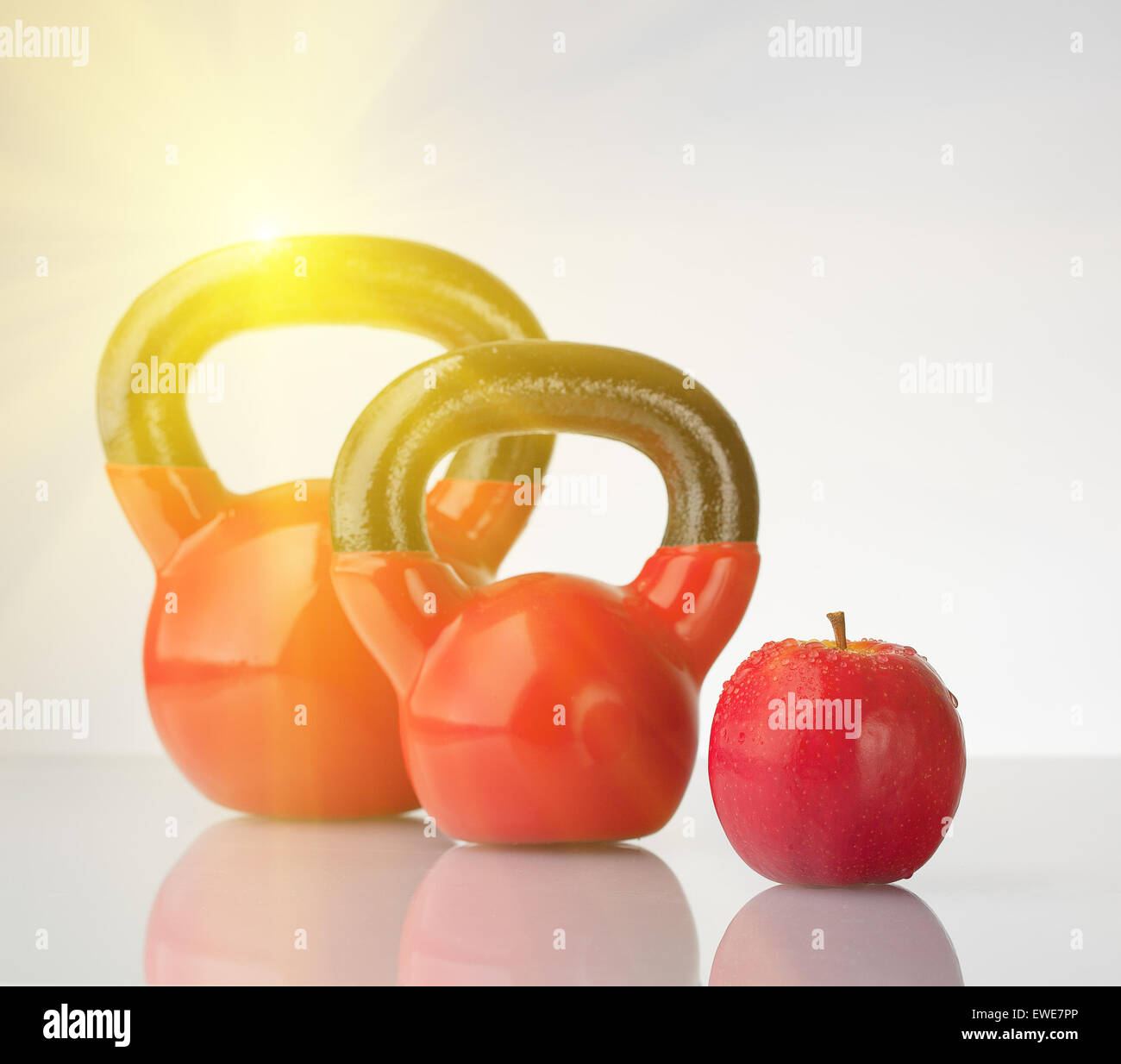 Red apple and kettlebells on reflective surface with flare - Stock Image
