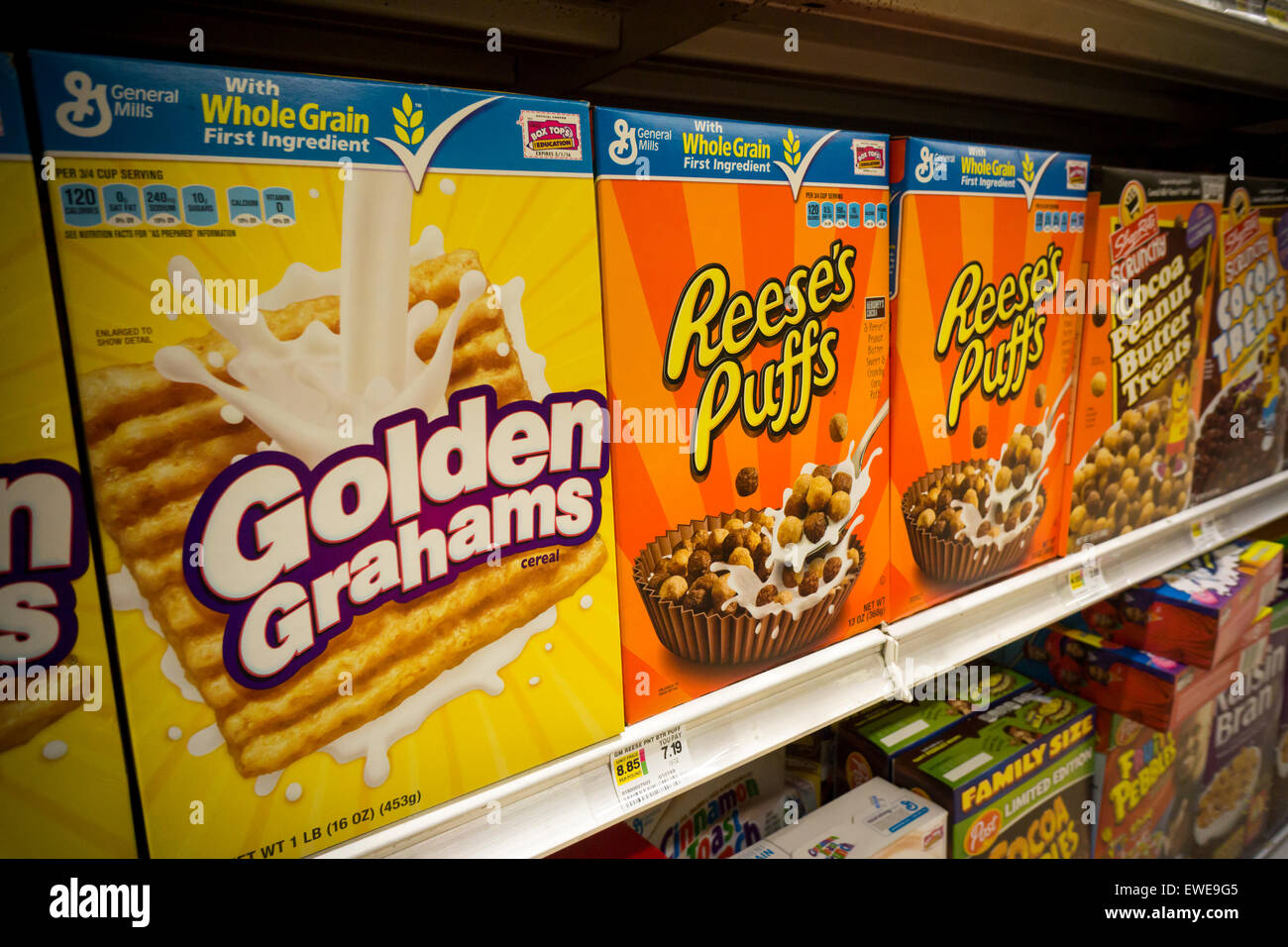 Boxes of General Mills breakfast cereals including Golden Grahams and Reese' Puffs displayed on supermarket - Stock Image