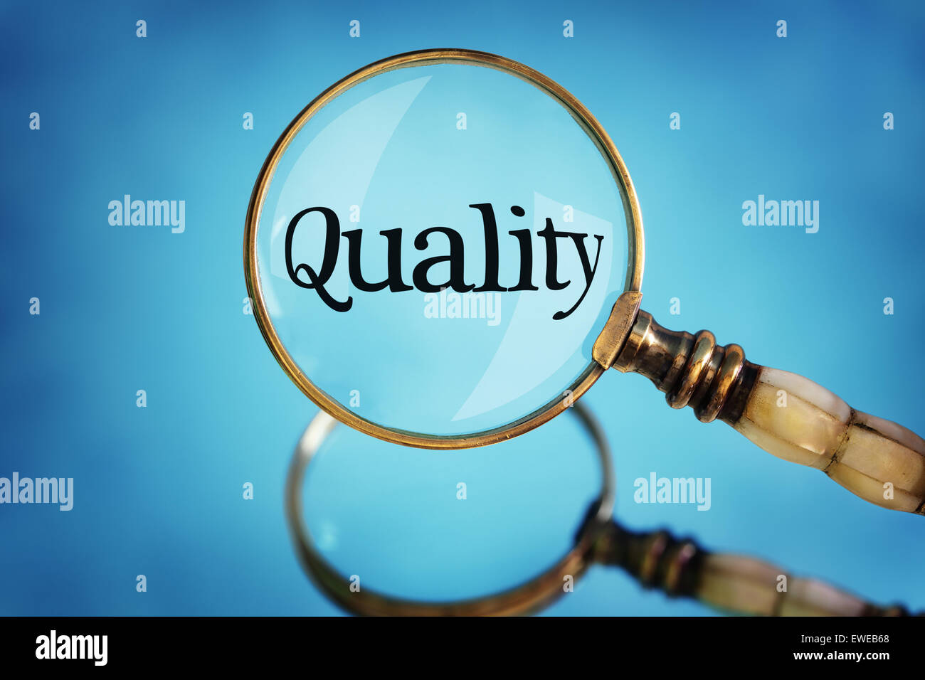 Magnifying glass focus on word quality - Stock Image