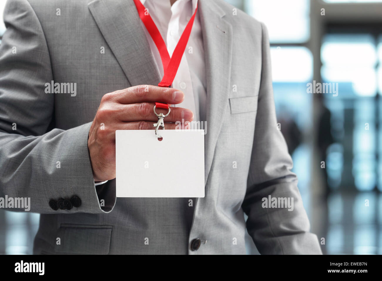 Businessman holding blank ID badge - Stock Image
