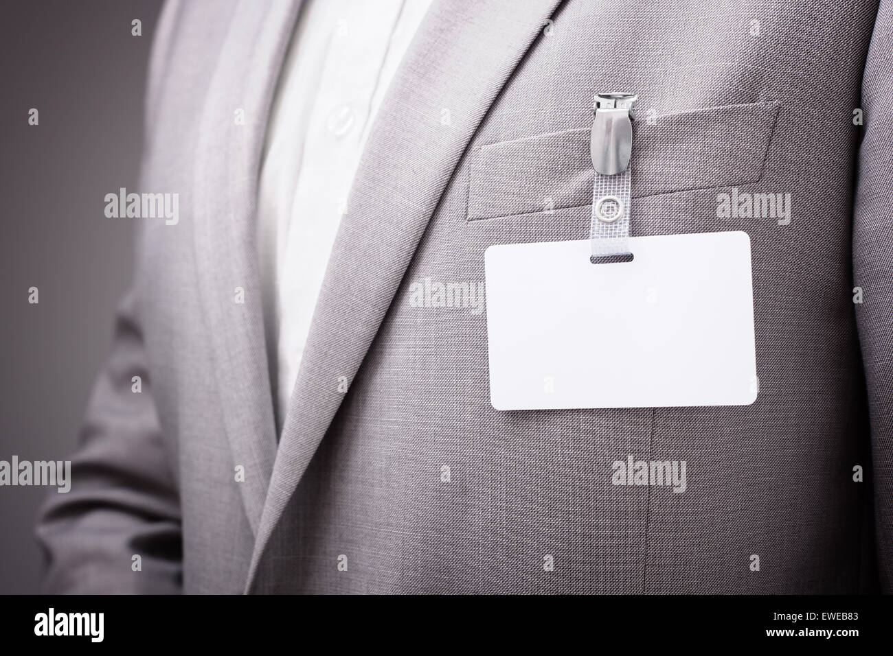 Businessman wearing blank name tag - Stock Image