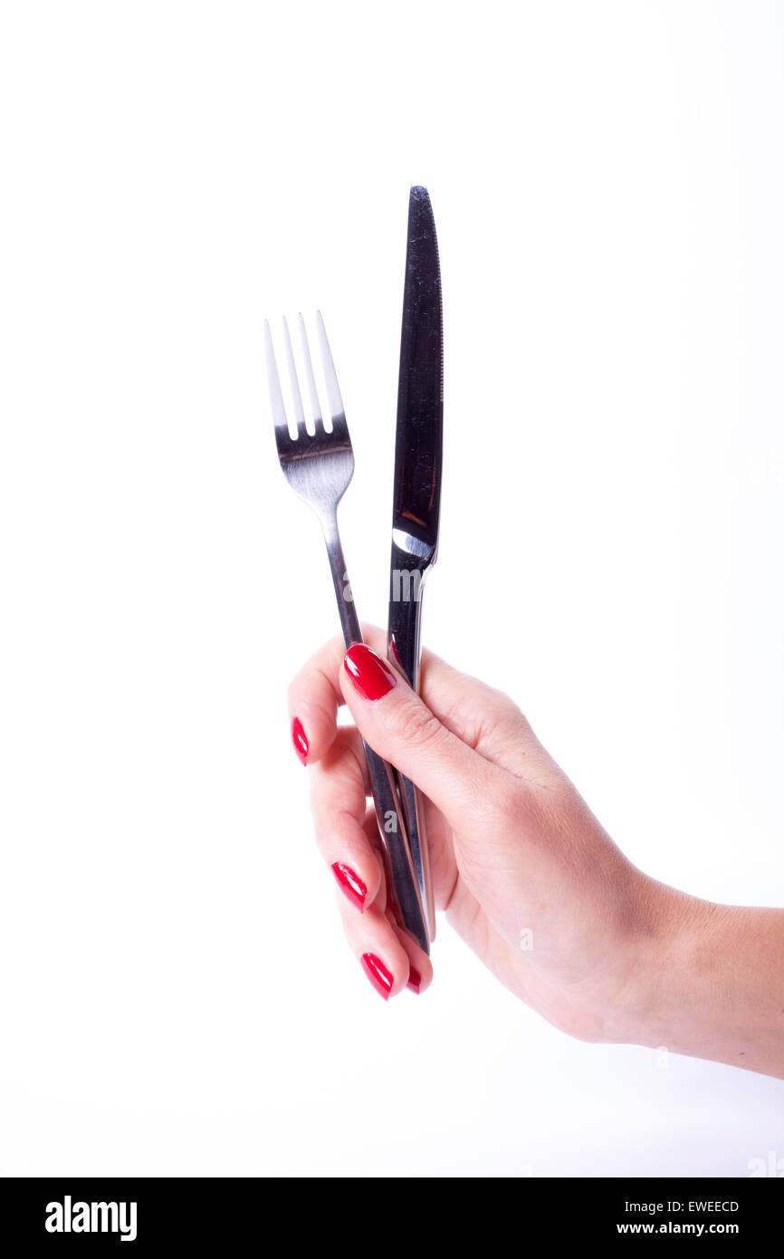 Woman hand with red manicure holding knife and fork - Stock Image