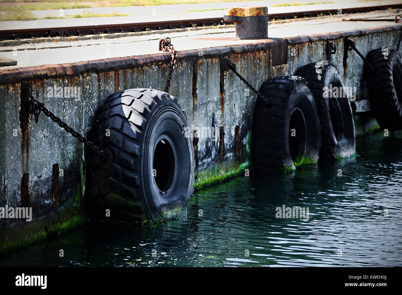 Big Truck Tires Used For Bump Stop In A Commercial Dock Stock Photo
