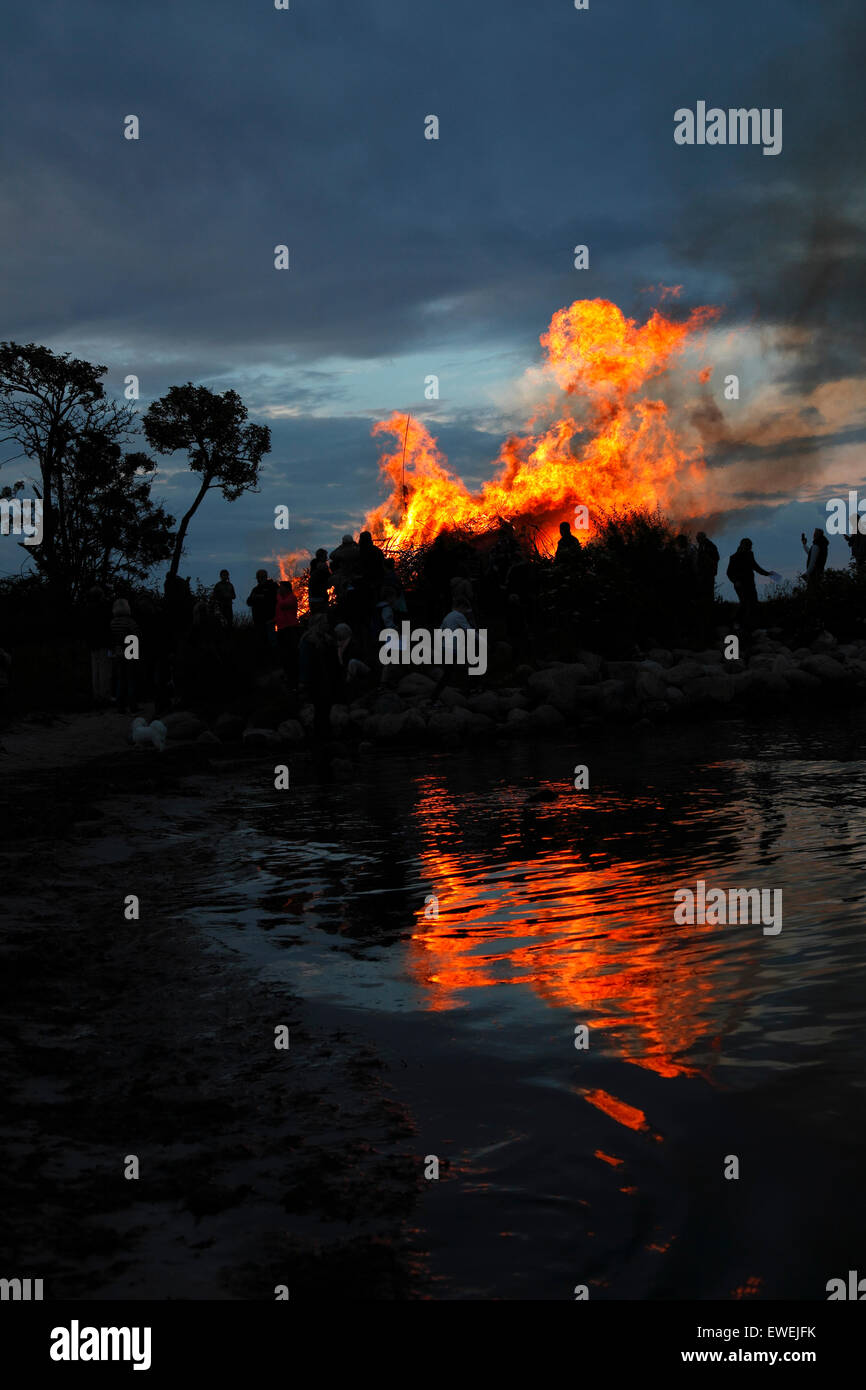 Bonfire on the beach at Nivaa Harbour in celebration of midsummer and St. John's Eve. Flames reflected in the - Stock Image