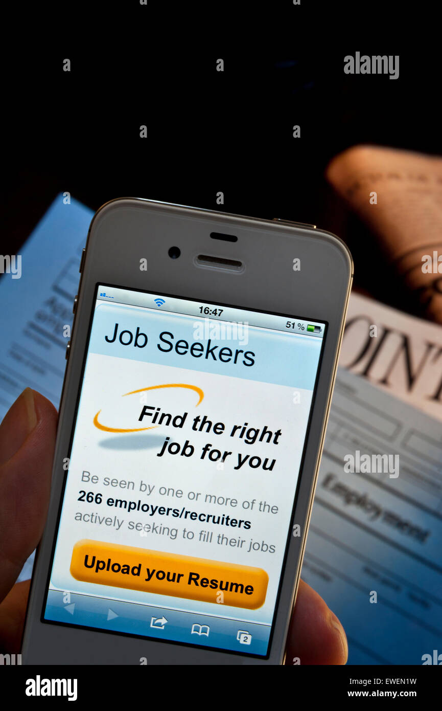Hand holding iPhone with job seekers CV upload screen app, employment forms and newspaper appointments pages on - Stock Image
