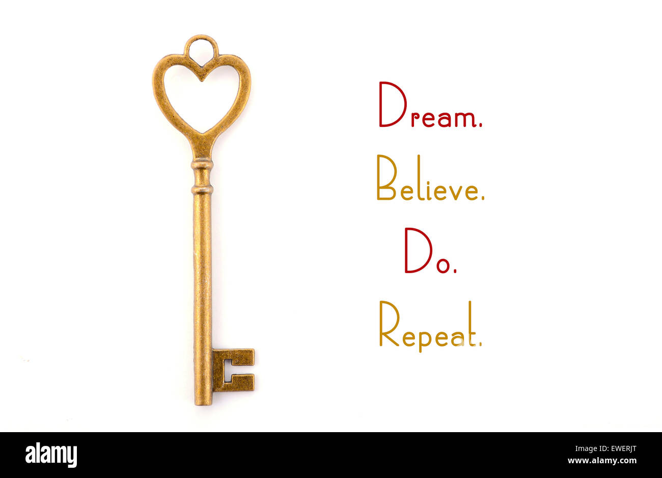 Gold heart shape key with inspirational phrase, dream believe do repeat. - Stock Image