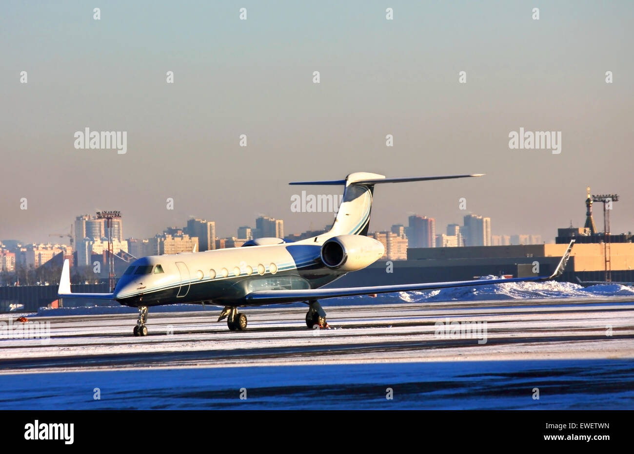 Twin-engined small jet on a parking place at the airport - Stock Image