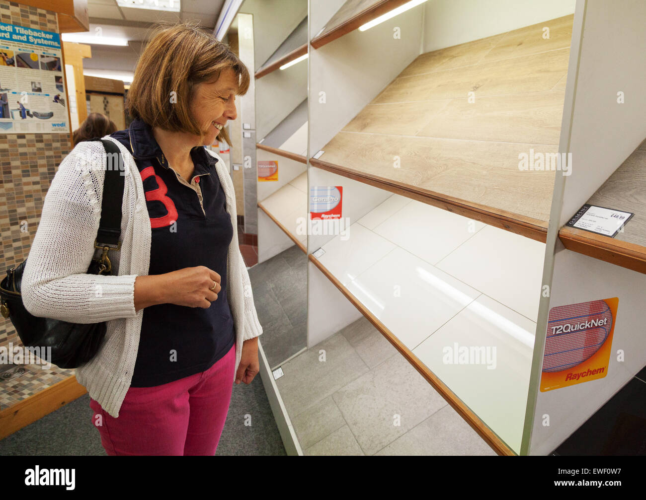 A middle aged woman shopping for floor tiles in a DIY store, UK - Stock Image