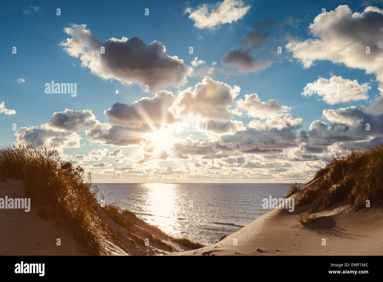Sunset landscape with sun,clouds and dunes - Stock Image