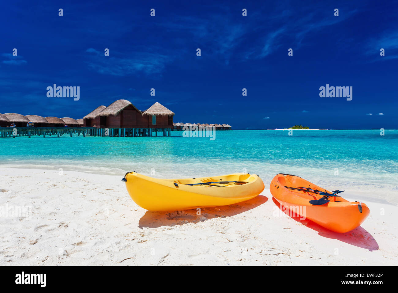Yellow and orangel kayaks on the tropical beach with vilas in background Stock Photo