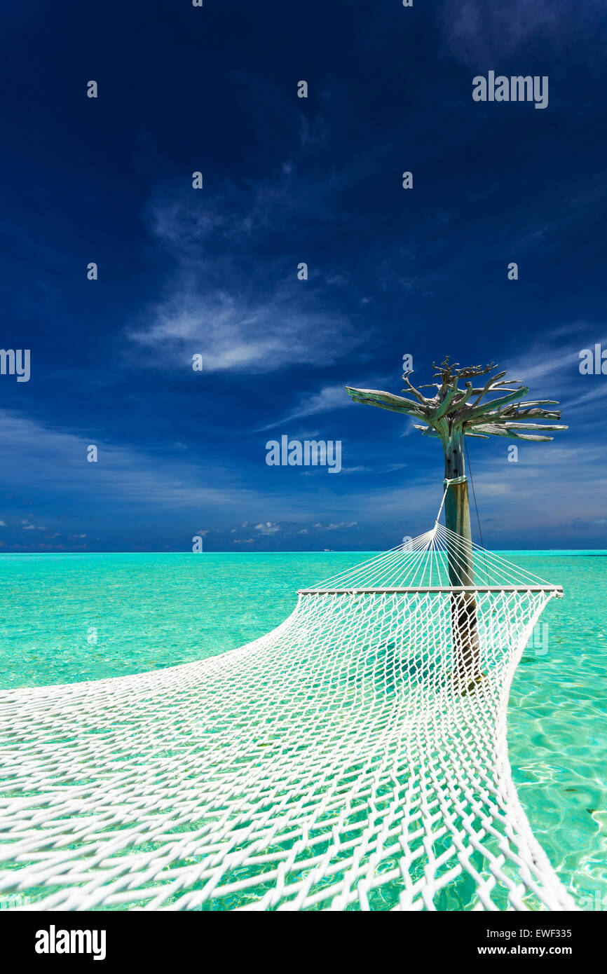 Empty over-water hammock in the middle of tropical lagoon in Maldives - Stock Image
