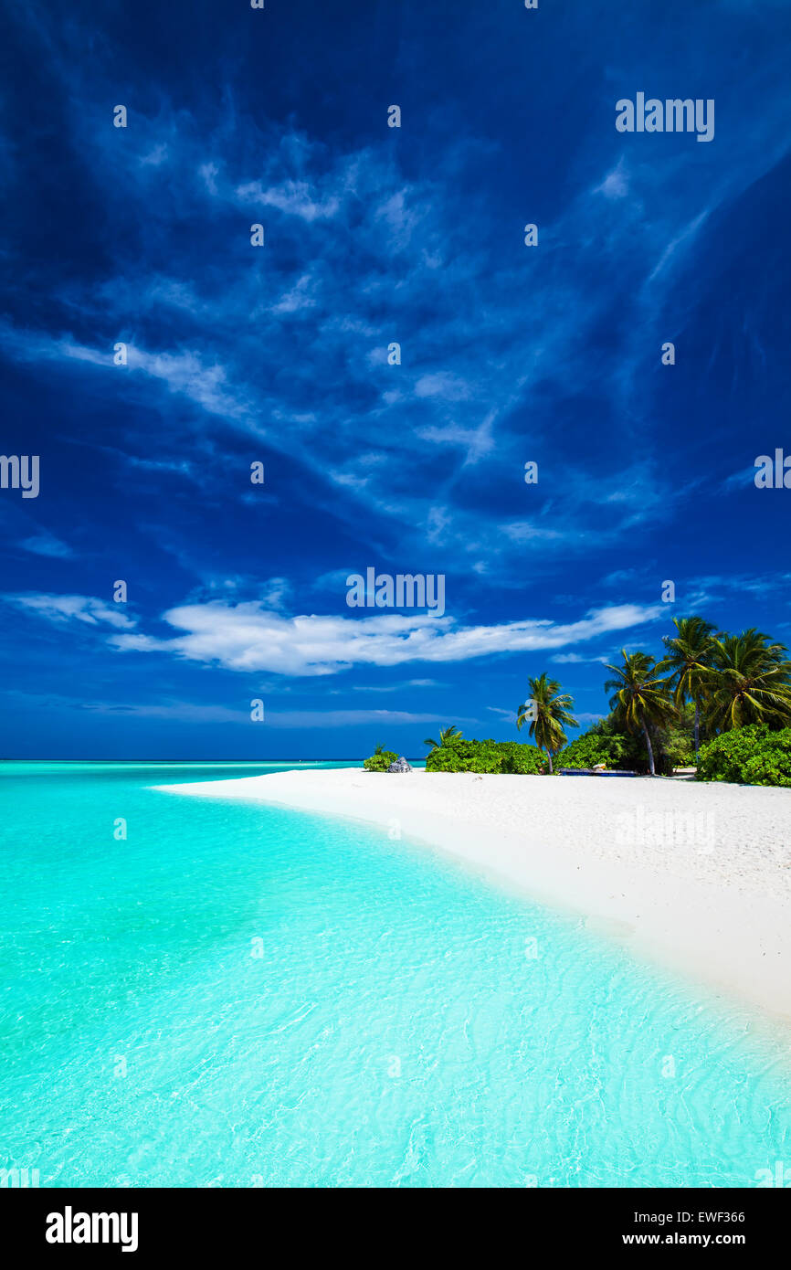 White tropical beach with beautiful sky with few palm trees and blue lagoon - Stock Image
