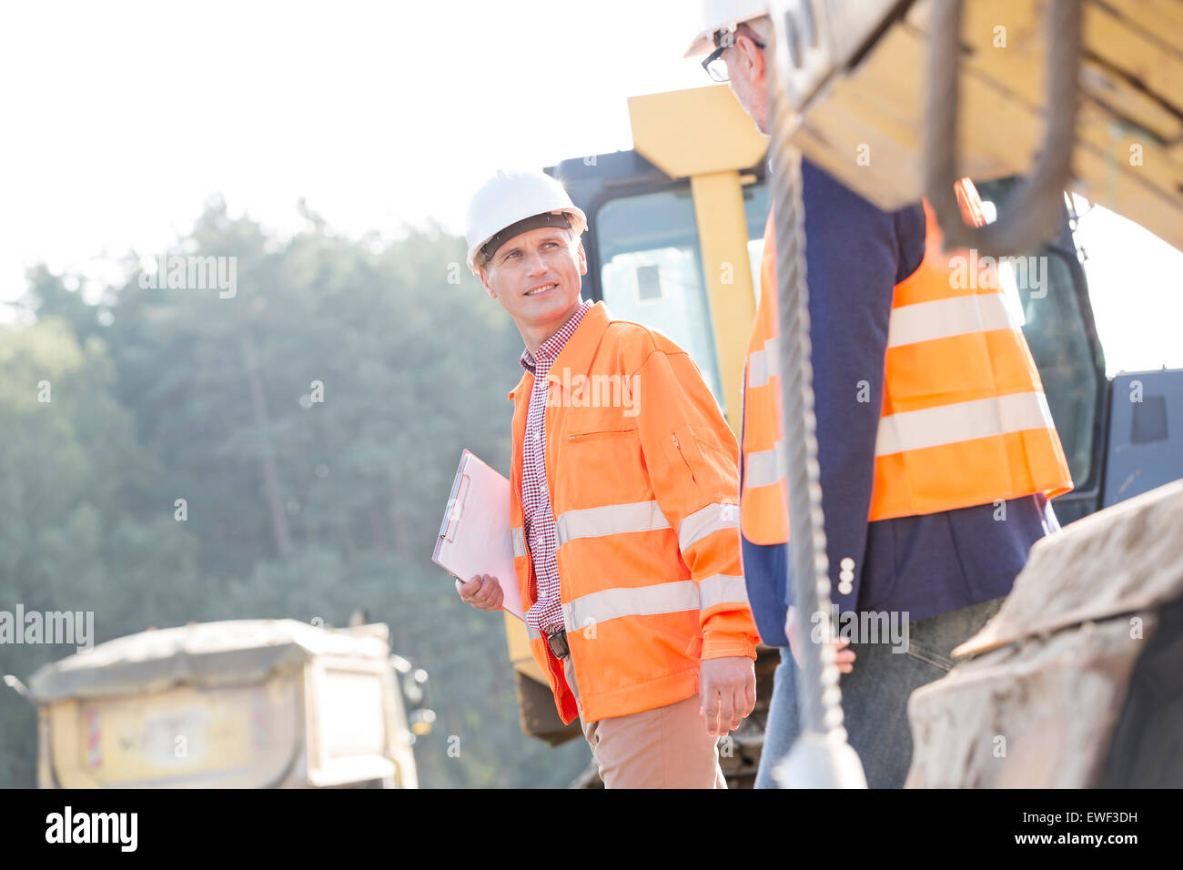 Supervisors discussing while walking at construction site - Stock Image