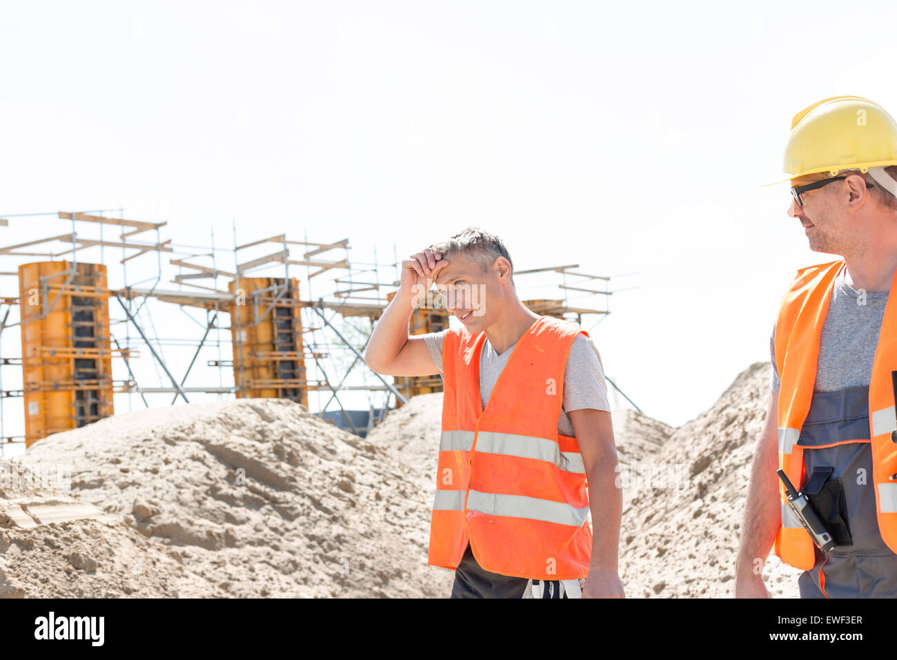 Construction worker looking at tired colleague wiping sweat at site Stock Photo